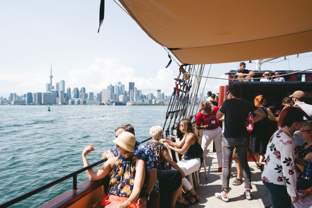 People sit, stand, and chat on a boat on a sunny day. Far behind them is the Toronto skyline.